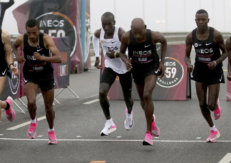 In this Oct. 12, 2019 photo, marathon runner Eliud Kipchoge from Kenya, white vest, wearing Nike AlphaFly prototype running shoe, and his first pacemaking team, wearing pink Nike Vaporfly shoes,  leave the start line on Reichsbrucke during the INEOS 1:59 Challenge attempt to run a sub two-hour marathon in Vienna, Austria. Nike has a new racing shoe; The Air Zoom Alphafly Next%, which was unveiled at a flashy fashion show in New York on Wednesday night, Feb. 5, 2020. Kipchoge wore a prototype of the shoe when he ran the world's first sub-2-hour marathon in an unofficial race in Octob(AP Photo/Ronald Zak, File)