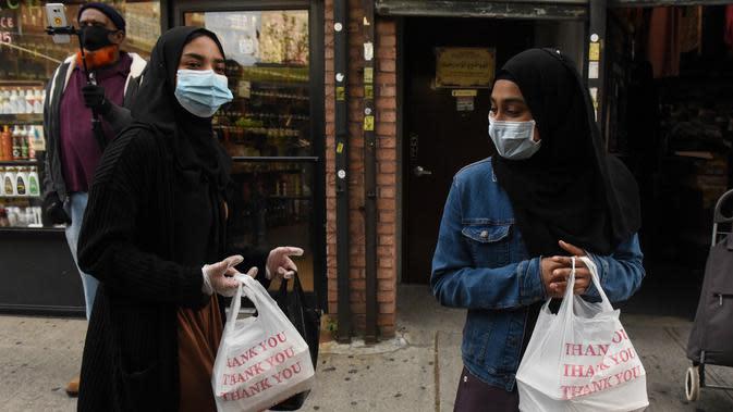 Dua wanita menerima makanan Halal gratis untuk Iftar selama bulan suci Ramadan di depan Masjid di masjid Taqwa, Brooklyn, New York (14/5/2020). Acara ini untuk menghormati ibu Wakil Advokat Publik Kashif Hussain meninggal karena COVID-19 pada 7 April 2020. (Stephanie Keith/Getty Images/AFP)