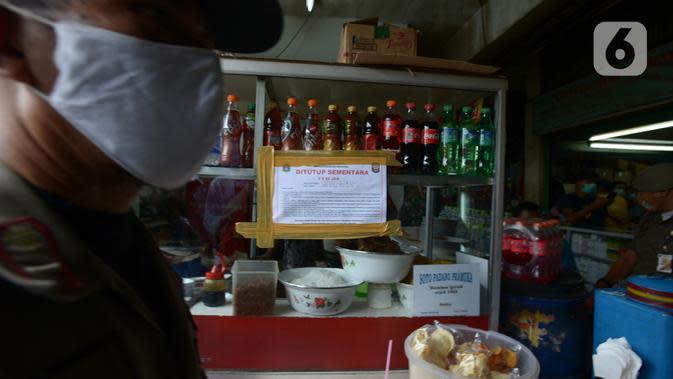 Segel penutupan sementara dipasang di salah satu tempat makan di Pasar Pramuka, Jakarta, Kamis (24/9/2020). Upaya mencegah penularan virus corona terus dilakukan dengan merazia pertokoan dan warung makan yang masih melayani makan di tempat. (merdeka.com/Imam Buhori)