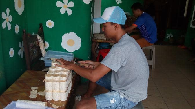 Perajin di Sentra Industri Tempe Sanan Malang, Jawa Timur, mengiris potongan tempe sebagai bahan baku keripik tempe (Liputan6.com/Zainul Arifin)