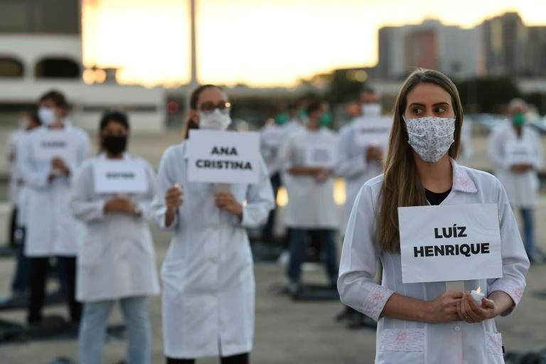 Brazilian nurses honour health workers who have died of the coronavirus at a demonstration in Brasilia