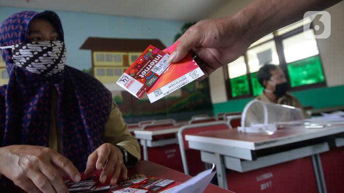 Wali murid menerima dua kartu perdana Tri dan Telkomsel beserta kuota gratis di SDN Serua Indah I dan II, Ciputat, Tangerang Selatan, Senin (15/9/2020). Program Kartu Perdana tersebut untuk mendukung kegiatan belajar secara online di masa pandemi covid-19. (merdeka.com/Dwi Narwoko)