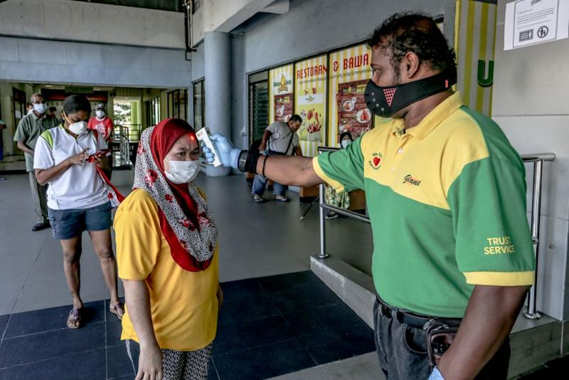 A Giant hypermarket staff screens members of the public on day nine of the movement control order in Kuala Lumpur March 26, 2020. — Picture by Firdaus Latif