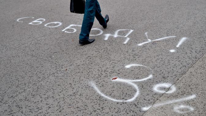 Seorang pria berjalan di halaman aspal yang dilukis dengan tulisan