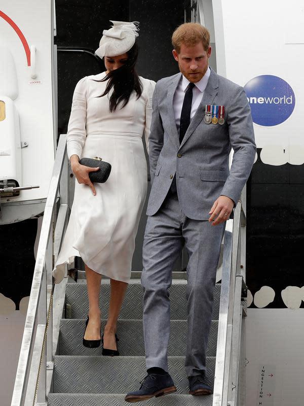 Pangeran Harry dan Meghan Markle turun dari pesawat saat tiba di Suva, Fiji, Selasa (23/10. Banyak fans yang merasa penasaran dengan jenis kelamin calon bayi sang Duchess of Sussex. (AP Photo/Kirsty Wigglesworth, Pool)