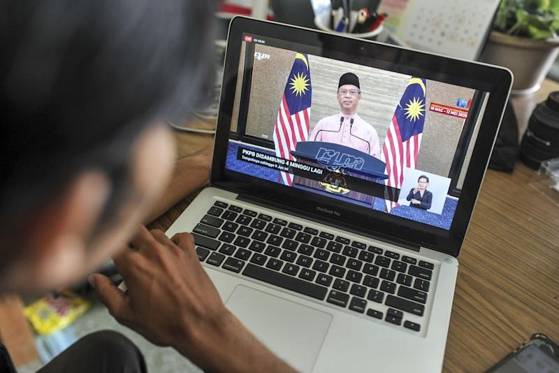 A man watch the live telecast of Prime Minister Tan Sri Muhyiddin Yassin speech about the conditional movement control order in Kuala Lumpur May 10, 2020. — Picture by Shafwan Zaidon