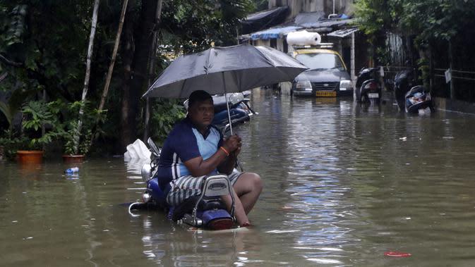 Seorang pria duduk duduk memegang payung di atas sepeda motor yang diparkir di jalan yang tergenang air setelah hujan lebat di Mumbai, India, Rabu (23/9/2020). Musim hujan di India berlangsung dari Juni hingga September. (AP Photo/Rajanish Kakade)