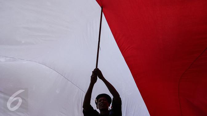 Seorang peserta 'Aksi Kita Indonesia' ikut membentangkan Bendera Merah Putih raksasa di Bundaran HI, Jakarta, Minggu (4/12). Aksi Kita Indonesia adalah acara perayaan kegembiraan atas keberagaman dan kebangsaan Indonesia. (Liputan6.com/Fery Pradolo)