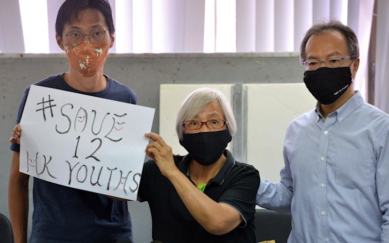 Ms Wong holds a sign at the press conference calling for the release of 12 activists detained while trying to flee the city - Peter PARKS / AFP
