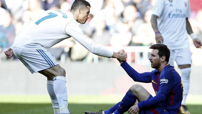 Pemain Real Madrid Cristiano Ronaldo membantu pemain Barcelona Lionel Messi untuk bangkit dalam laga El Clascio Liga Spanyol di Santiago Bernabeu, Sabtu (23/12/2017). Barcelona menang 3-0 di laga itu. (AP Photo / Francisco Seco)