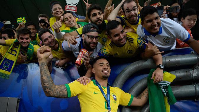 Striker Timnas Brasil, Gabriel Jesus berpose bersama penggemar saat merayakan gelar juara Copa America 2019 setelah mengalahkan Peru pada partai final di Maracana Stadium, Senin (8/7/2019) dini hari WIB. Brasil sukses mengangkat trofi Copa America 2019 usai mengalahkan Peru 3-1. (Juan MABROMATA/AFP)