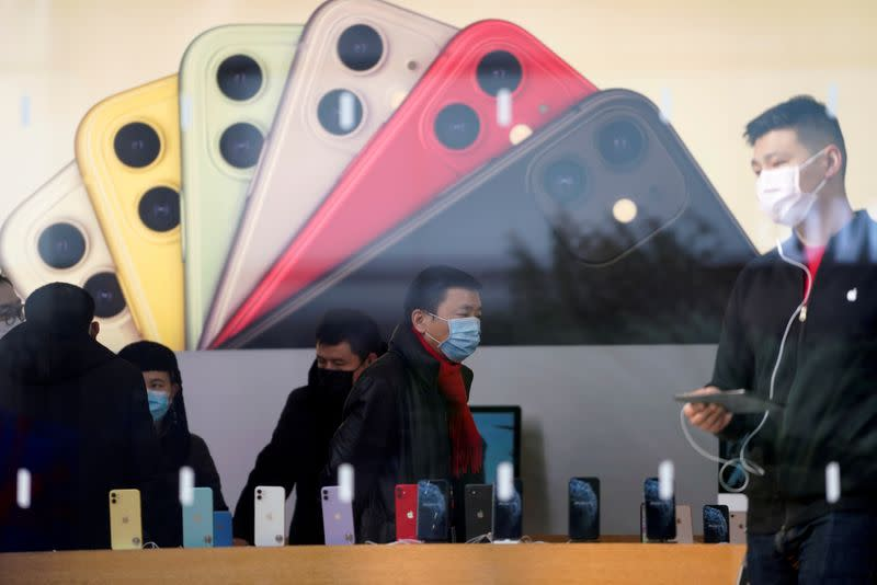 FILE PHOTO: People wearing protective masks are seen in an Apple Store, as China is hit by an outbreak of the new coronavirus, in Shanghai