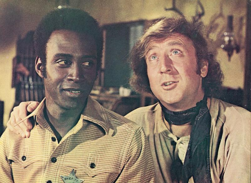 Gene Wilder puts his arm around the shoulder of Cleavon Little in a still from the 1974 film 'Blazing Saddles'. (Photo by Warner Bros/Courtesy of Getty Images)