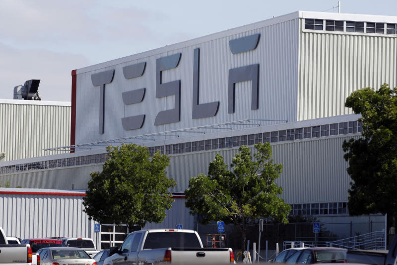 FILE -This June 22, 2012, file photo, shows an exterior view of the Tesla factory in Fremont, Calif. The parking lot was full at Tesla's California electric car factory Monday, May 11, 2020, an indication that the company was resuming production in defiance of an order from county health authorities.  (AP Photo/Paul Sakuma, File)