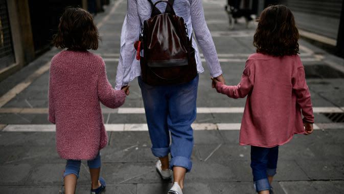 Keluarga berjalan-jalan di sepanjang jalan kota lama, di Pamplona, Spanyol utara (27/4/2020). Anak-anak di bawah 14 tahun diizinkan untuk berjalan-jalan dengan orang tua hingga satu jam dan dalam satu kilometer dari rumah, mengakhiri enam minggu pembatasaan. (AP Photo/Alvaro Barrientos)