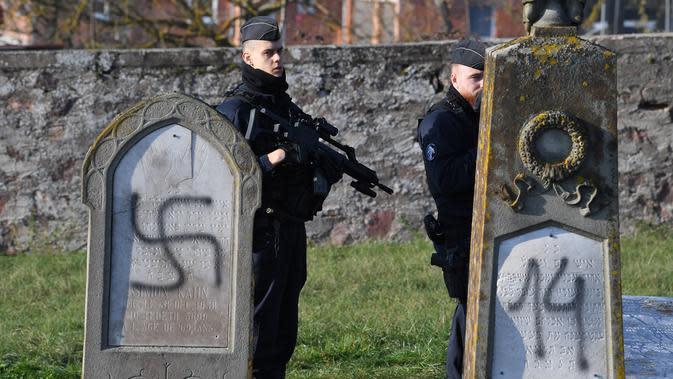 Aparat kepolisian melakukan penjagaan di sekitar kompleks pemakaman Yahudi yang menjadi sasaran aksi vandalisme, Westhoffen, dekat Strasbourg, Prancis, Rabu (4/12/2019). Sedikitnya 107 makam menjadi sasaran vandalisme dengan dicoreti lambang swastika Nazi. (AFP/Patrick Hertzog)
