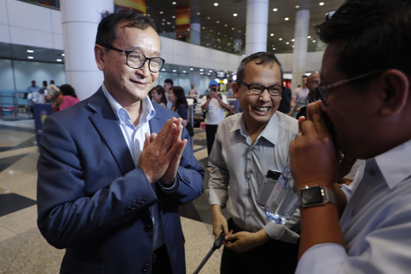 CORRECTS LOCATION - Cambodia's exiled opposition leader Sam Rainsy, left, greets supporters as he arrived at Kuala Lumpur International's Airport in Sepang, Malaysia Saturday, Nov. 9, 2019. Sam Rainsy landed in Kuala Lumpur in a bid to return to his homeland after Thailand had earlier blocked him from entering. (AP Photo/Vincent Thian)