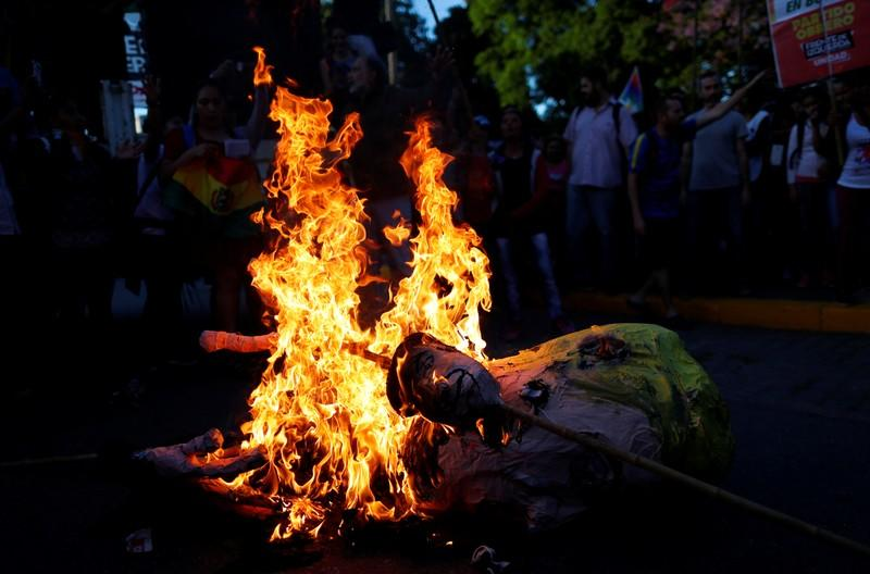 An effigy depicting U.S. President, Donald Trump is set on fire by supporters of Bolivia's ousted President Evo Morales outside the U.S. embassy in Buenos Aires to protest against the U.S. government, in Buenos Aires