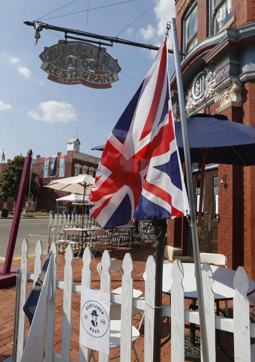 In this Sept. 5, 2013, photo a British flag hangs outside the Bluebell Saloon and Restaurant in Guthrie,, Okla. The population of the small Oklahoma town is expected to quadruple this weekend as people come to watch the British folk rock band on the second stop of the Mumford & Sons' Gentlemen of the Road concert series in Guthrie. (AP Photo/Sue Ogrocki)