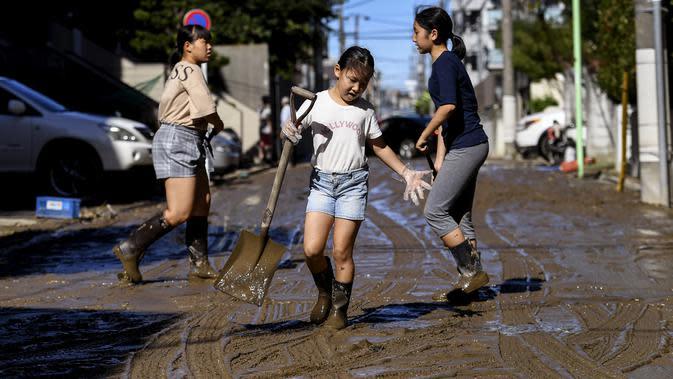 Anak-anak membersihkan lumpur dari jalan setelah banjir surut di Kawasaki, Minggu (13/10/2019). Topan dahsyat Hagibis yang menerjang sejumlah wilayah di Jepang menyebabkan banjir di beberapa lokasi. (Photo by WILLIAM WEST / AFP)