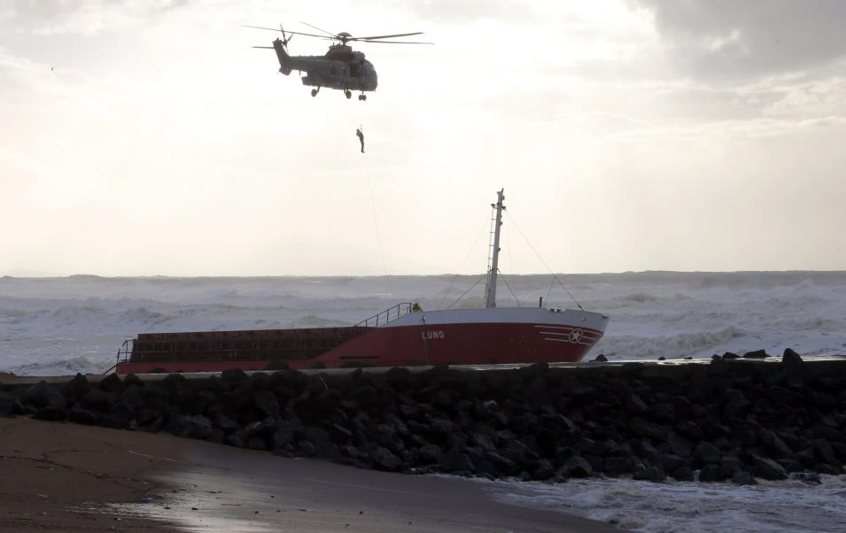 A member of the French military is hoisted by helicopter after inspecting an empty Spanish cargo ship which broke in two on a seawall off the beach in Anglet