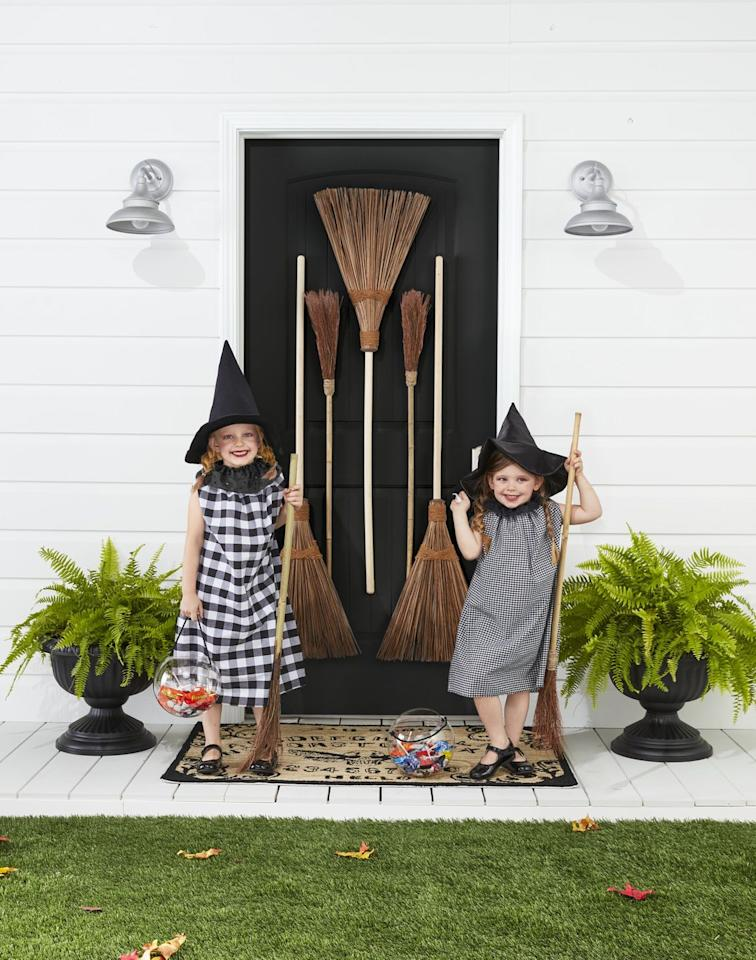 "<p>Start a country coven! Gussied up in black-and-white gingham, these sweet witches are ready to cast some serious spells on Halloween night.</p><p><strong>Make the Costumes: </strong>Cut two 31- by 20-inch rectangles from black-and-white gingham fabric. Sew ends together, leaving armholes toward the top of the rectangle. Fold in the top 1 inch of the fabric and sew a channel, leaving a 1-inch opening. Thread a ribbon or string through the channel. Once on, pull the ribbon to gather it at the top. Cut a 3 1/2- by 36-inch strip from black eyelet fabric. Sew a hand-running stitch along the edge of one of the long sides. Leave a knot at one end and pull the string on the other side to create gathers. Pin at the back of the costume or add a snap. Finish with witches hats.</p><p><a class=""body-btn-link"" href=""https://www.amazon.com/Womens-Costume-Accessory-Halloween-Carnivals/dp/B01LXQ76K1?tag=syn-yahoo-20&ascsubtag=%5Bartid%7C10050.g.28304812%5Bsrc%7Cyahoo-us"" target=""_blank"">SHOP WITCHES HATS</a></p>"