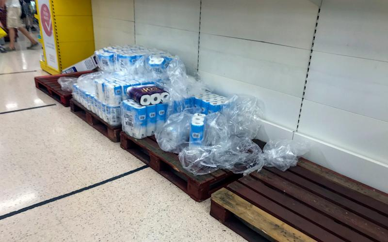 Stockpiling part two - depleted stocks and empty pallets in the toilet roll aisle at the Portsmouth North Harbour Tesco - Steve Parsons/PA Wire
