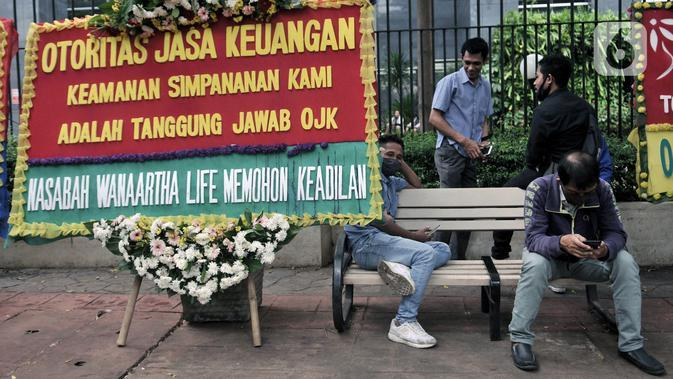 Warga duduk dekat karangan bunga dari korban asuransi Jiwasraya yang terpajang di depan Gedung Pengadilan Tipikor, Jakarta, Rabu (3/6/2020). Puluhan karangan bunga tersebut berisi harapan para korban agar kasus segera tuntas dan uang mereka dapat kembali. (merdeka.com/Iqbal S. Nugroho)