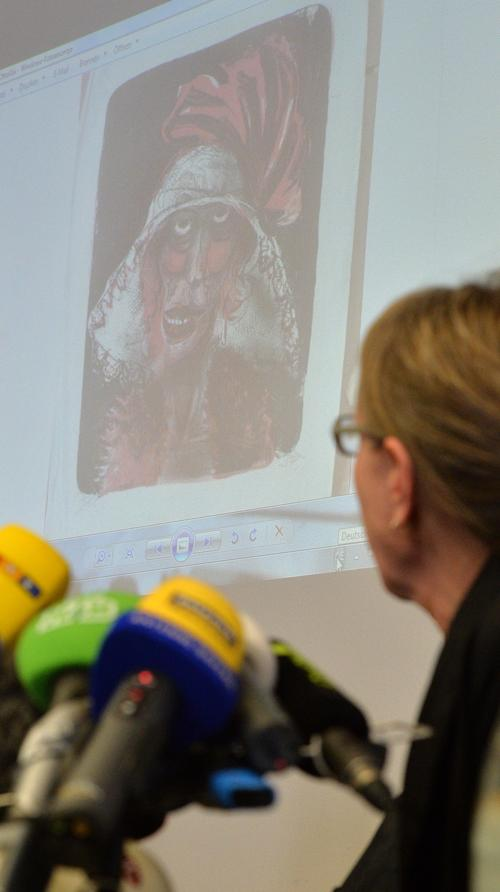 Expert and art historian Meike Hoffmann from the Berlin Free University looks at a projected painting of Otto Dix during a news conference in Augsburg, southern Germany, Tuesday, Nov. 5, 2013, on the art found in Munich. A hoard of more than 1,400 art works found last year at a Munich apartment includes previously unknown pieces by artists including Marc Chagall, German investigators said Tuesday, adding that they face a hugely complicated task to establish where the art came from. (AP Photo/Kerstin Joensson)
