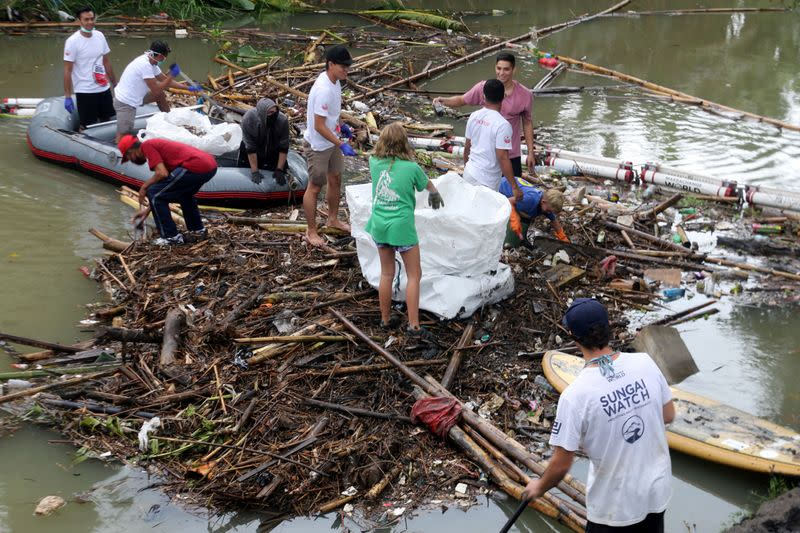 Volunteers collect trash trapped by barriers, which are called 'trash boom', at a river in Badung
