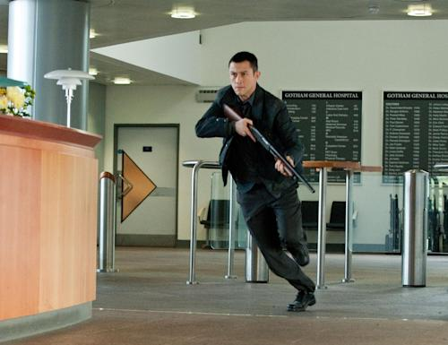 """In this publicity photo provided by Warner Bros. Pictures, Joseph Gordon-Levitt as John Blake is shown in a scene in Warner Bros. Pictures' and Legendary Pictures' action thriller """"The Dark Knight Rises."""" After the theater shooting in Colorado on July 20, 2012 at the film's midnight screening, Warner Bros. quickly pulled a trailer for its upcoming film """"Gangster Squad."""" The new movie features a star-studded cast, along with a climactic scene in which mobsters fire automatic weapons into a movie theater audience from behind the screen. (AP Photo/Warner Bros. Pictures, Ron Phillips)"""