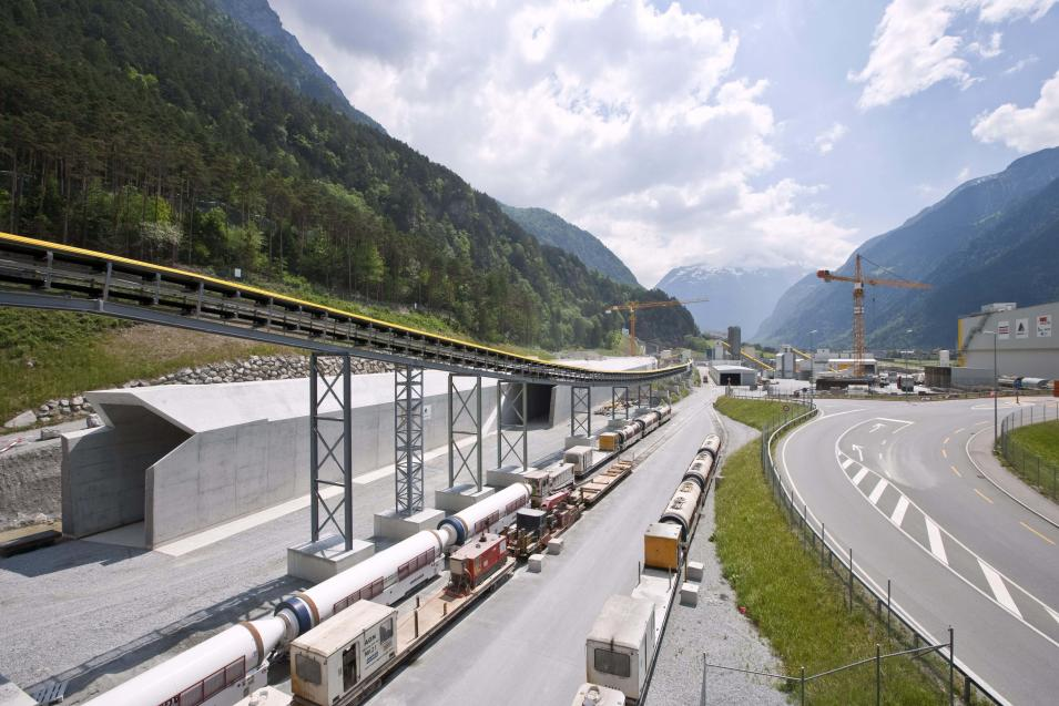 """This May 29, 2009 photo shows the entrance to the """"Erstfeld"""" north portal of the Gotthard Base Tunnel (background) and a conveyor belt for the excavated material (front), near Erstfeld in the canton of Uri, Switzerland. The company in charge of the project says there are only 59 feet (18 meters) left to dig before completing the last section of the new Gotthard Base Tunnel. When it is opened for traffic in 2017, the Gotthard Base Tunnel will supplant Japan's 33.5-mile (53.6-kilometer) Seikan Tunnel as the world's longest _ excluding aqueducts _ and allow millions more tons of goods to be transported quickly through the Alps by rail.  (AP Photo/Keystone, Gaetan Bally) *** NO SALES, NO ARCHIVES ***"""