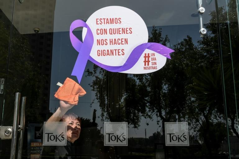 A woman cleans the glass door of a Mexico City restaurant with a sign reading 'We stand with those who make us giants' during Monday's 'A Day Without Us' protest