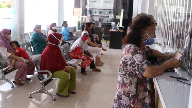 Nasabah menghitung uang saat di Pegadaian Kota Tangerang, Banten, Kamis (4/6/2020). Memasuki tahun ajaran baru yang jatuh pada 13 Juli 2020, warga ramai menggadaikan barang mereka untuk persiapan masuk sekolah anak. (Liputan6.com/Angga Yuniar)