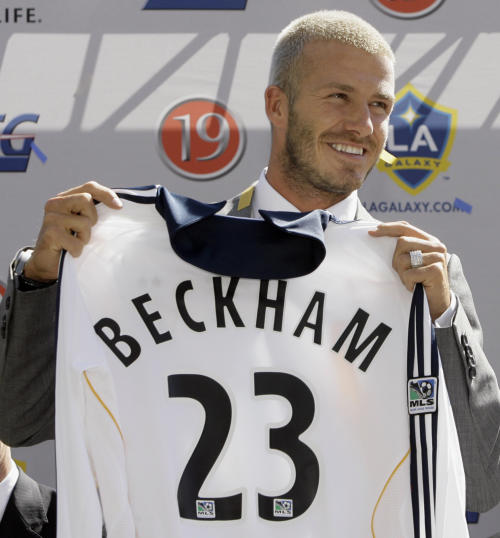 FILE - In this July 13, 2007, file photo, England soccer player David Beckham holds up his new jersey as he is introduced as the newest member of the Los Angeles Galaxy soccer team in Carson, Calif. The 38-year-old midfielder, who recently won a league title in a fourth country with Paris Saint-Germain, said Thursday, May 16, 2013, he will retire after the season. (AP Photo/Nick Ut, File)