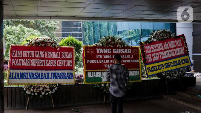 Seorang pria berdiri di depan karangan bunga dukungan di halaman Kementerian BUMN Jakarta, Kamis (16/1/2020). Kantor Menteri BUMN Erick Thohir kembali mendapat kiriman bunga berupa dukungan untuk menyelesaikan masalah PT Asuransi Jiwasraya (Persero). (Liputan6.com/Faizal Fanani)