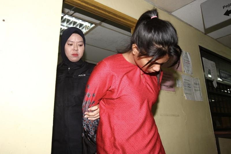 Nurul Shamira Mazlan, who was accused of murdering her two-year-old daughter, is escorted from the Magistrate's Court in Johor Baru January 22, 2020. — Picture by Ben Tan