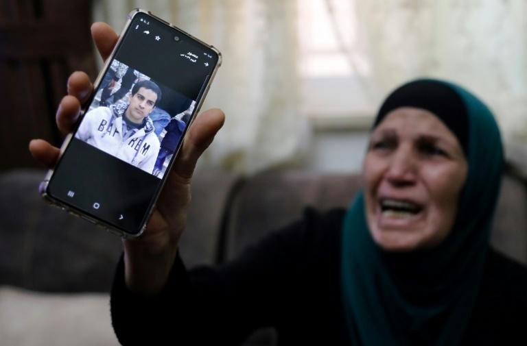 The mother of the Palestinian man shot dead by Israeli police shows his picture at her home in annexed east Jerusalem
