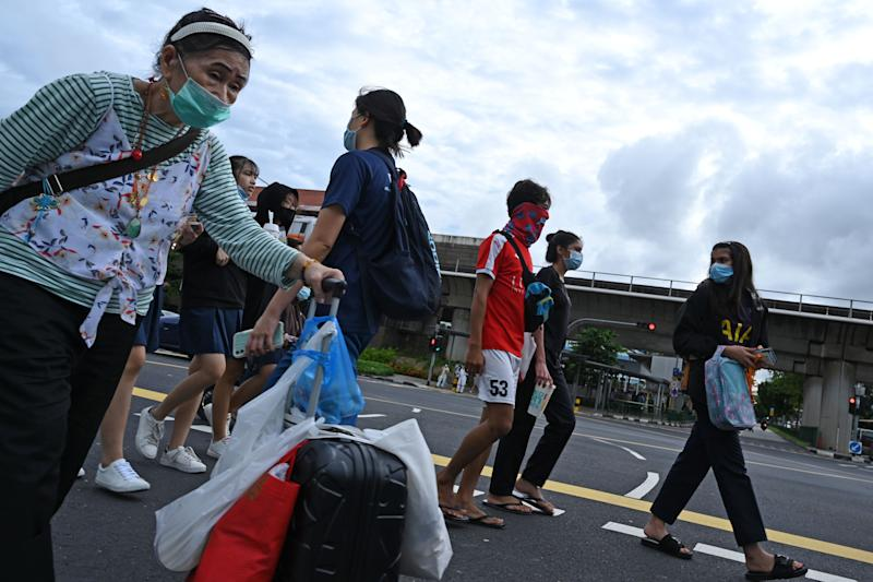 """People cross a street in Singapore on June 23, 2020. - Singapore's Prime Minister Lee Hsien Loong called a general election """"like no other"""" on June 23 as the city-state struggles to recover from a major coronavirus outbreak that has swept through crowded migrant worker dormitories. (Photo by Roslan RAHMAN / AFP) (Photo by ROSLAN RAHMAN/AFP via Getty Images)"""