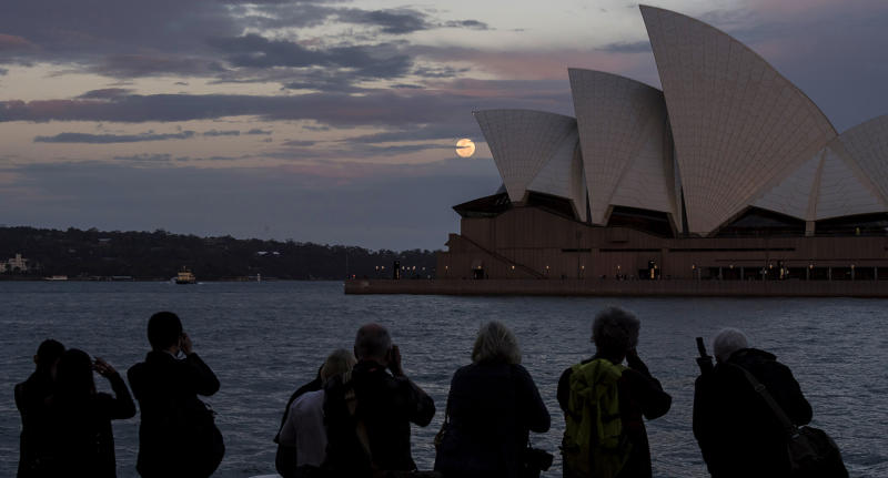 Photo shows people looking at the full moon over the Sydney Opera House.