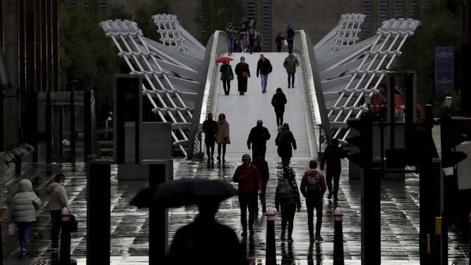 Orang-orang berjalan melintasi London Millennium Footbridge di London, Kamis (15/10/2020). London akan dipindahkan ke penguncian Tingkat 2 akibat virus corona COVID-19. (AP Photo/Matt Dunham)