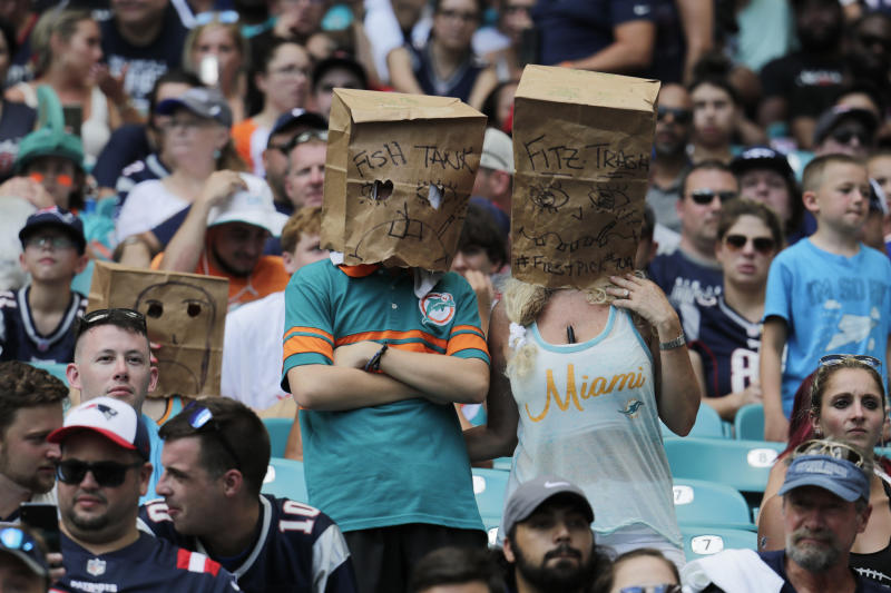 Unhappy Miami Dolphins fans wear paper bags during a 43-0 loss to the Patriots. (AP)