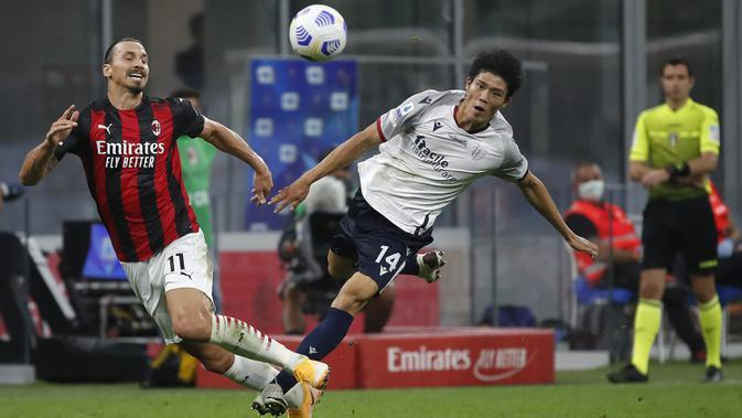 Pemain AC Milan Zlatan Ibrahimovic (kiri) berebut bola dengan pemain Bologna Takehiro Tomiyasu pada pertandingan Serie A di Stadion San Siro, Milan, Italia, Senin (21/9/2020). AC Milan menaklukkan Bologna 2-0. (AP Photo/Antonio Calanni)