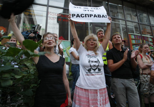 "Supporters of members of feminist punk group Pussy Riot shout ""Freedom Pussy Riot"" during an action at a court room in Moscow, Russia, Monday, Aug. 6, 2012. The woman wears a T-shirt with President Vladimir Putin's picture and the inscription: ""A very dangerous criminal wanted. Reward: A free Russia."" holds a poster that reads: ""This is not the court, this is a lynching!"" Members of a feminist Russian punk band on trial for performing a stunt against Vladimir Putin in Moscow's main cathedral sought to dismiss their judge on Monday, accusing him in court of being politically biased and ignoring their side of the story. (AP Photo/Alexander Zemlianichenko)"