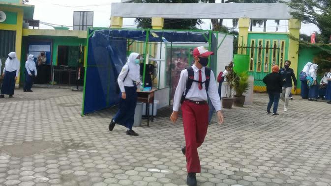 Sejumlah anak sekolah di SMPN 1 Kota Jambi mulai masuk sekolah pertama saat masa pandemi, Senin (13/7/2020). Meski status Kota Jambi zona kuning, Pemkot Jambi telah mengizinkan belajar mengajar tatap muka. (Liputan6.com / Gresi Plasmanto)