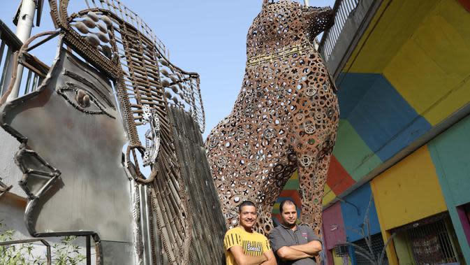 Ibrahim Salah (kiri) dan Ahmed Hussein berfoto di bengkel kerja mereka di Giza, Mesir, 5 September 2020. Keduanya berhasil mengubah hobi mereka mendaur ulang barang bekas seperti besi tua menjadi berbagai dekorasi dan furnitur rumah sebagai sumber penghasilan yang stabil. (Xinhua/Ahmed Gomaa)