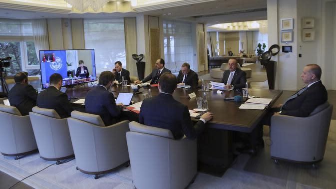 Presiden Turki Recep Tayyip Erdogan (kanan) diapit oleh para menterinya dan penasihatnya mengikuti KTT Luar Biasa G20 secara virtual dari Istanbul, Turki, Kamis (26/3/2020). Para pemimpin dunia mengkoordinasikan respons global terhadap pandemi virus corona COVID-19. (Turkish Presidency via AP, Pool)