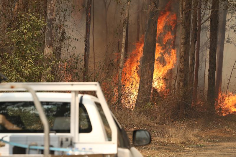 Local residents are seen near a bushfire burning next to Busby's Flat Road in Busbys Flat, northern NSW, Wednesday, October 9, 2019. (AAP Image/Jason O'Brien) NO ARCHIVING