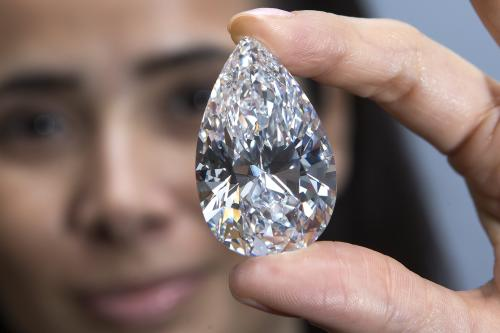 FILE -In this April 30, 2013 file picture a Christie's employee displays the largest colour flawless diamond, weighing 101.73 carats, during a preview at Christie's auction house in Geneva, Switzerland,. The largest pear-shaped colour flawless diamond is expected to reach US $ 30 million and it will be the hightlight at the Christie's auction on Wednesday May 15 , 2013 in Geneva. (AP Photo/keystone, Salvatore Di Nolfi,File)