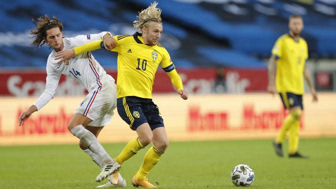 Gelandang Prancis, Adrien Rabiot, berebut bola dengan pemain Swedia, Emil Forsberg, pada laga UEFA Nations League di Friends Arena, Minggu (6/9/2020). Prancis menang 1-0 atas Swedia. (Christine Olsson/TT via AP)